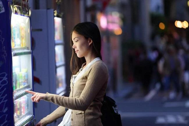 一女性在自动售货机上购买商品
