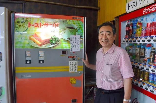 自助餐厅老板中岛薰和自动贩卖机。(图片来源:日本《朝日新闻》网站)